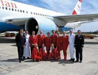die crew der austrian airlines posiert in uniform für ein foto vor einem flugzeug
