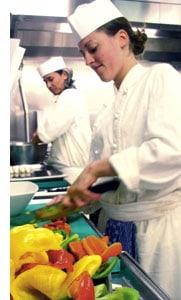 Frauen in der Küche schneiden Gemüse klein