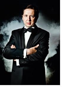 Heinz Reitbauer mit verschränkten Armen im schwarzen Anzug