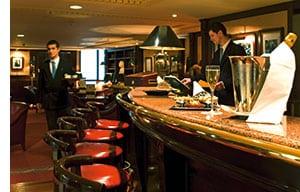 ein blick an die hotelbar, waehrend der barkeeper drinks vorbereitet, bringt der kellner sie zu den tischen