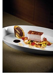 Schweinebauch mit Erdäpfel-Blunzen-Roulade und Kümmeljus auf Tomatenkraut