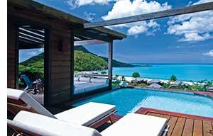 karibisches Paradies, weisse Sonnenliegen, ein Pool mit Ausblick aufs Meer, luxurioese Unterkunft