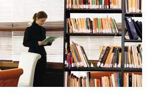 eine Frau neben einem Bücherregal, stehend und lesend