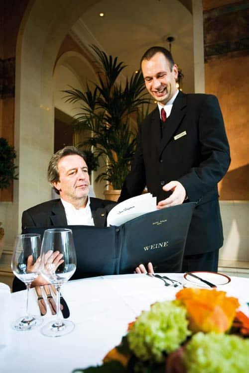 Gast mit der Weinkarte, während der Sommelier ihn beratet