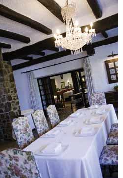 ein Tisch mit weissem Gedeck und romantisch-blumig verzierte Stühle