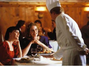 zwei damen sitzen in einem restaurant, während der koch ihnen die speise bringt himmeln sie ihn an