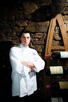 Thomas Dorfer mit verschränkten Armen und ernster Miene im Weinkeller