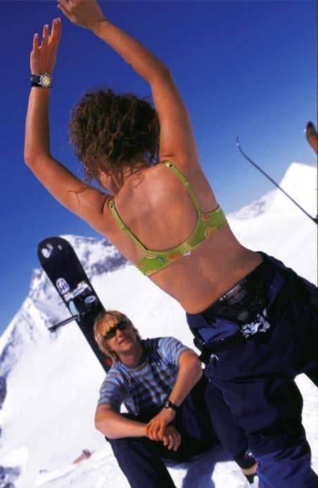 Eine Frau im Bikinioberteil und Snowboardhose tanzt auf dem Berg während ein Herr vor ihr sitzt und ihr dabei zusieht
