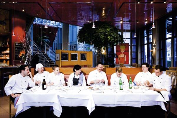 Alexander Tschebul auf einer langen Tafel sitzend mit seinem Team
