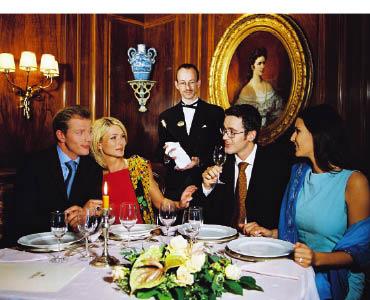 Zwei Liebespaare sitzen in einem Restaurant, unterhalten sich. und verkosten Wein während sich der Kellner mit der Flasche im Hintergrund aufhält