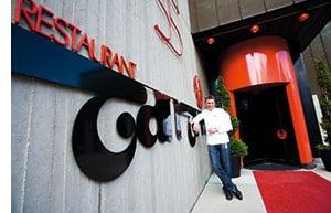 Hans Haas vor dem Logo ueber der Eingangstuer seines Restaurants