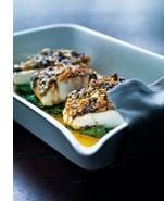 Weißer Heilbutt mit Oliven-Krokant-Kruste auf gedämpftem Spinat und Orangen-Pfeffer-Butter
