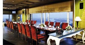 lange Tafel im Konferenzsaal, bodentiefe Fenster, rote Stoffstühle