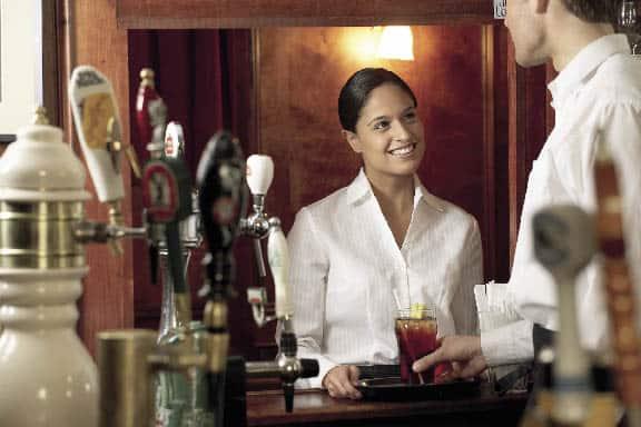 eine Frau und ein Mann sehen sich an, während er ihr den Cocktail aufs Tablett stellt
