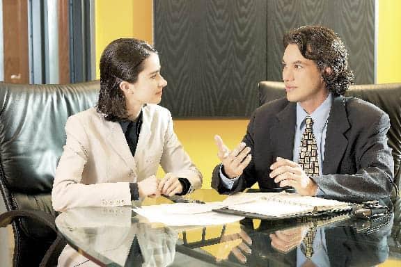 eine Frau und ein Mann unterhalten sich in einem Büro
