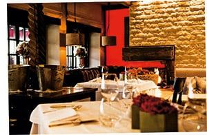ein Einblick in ein Restaurant, klassisch gedeckter Tisch, Naturstein an den Wänden