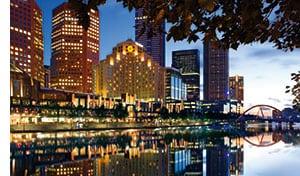 die beleuchteten Wolkenkratzer der Stadt spiegeln sich im Wasser des Hafens