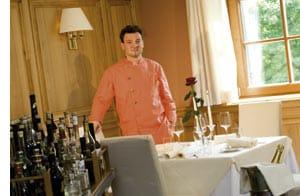 Didi Dorner in orange-farbenem Kochgewand im Restaurant stehend