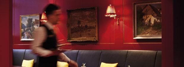 tiefrote Wände, blauer Pölstermöbel, der Kellner in Bewegung, ein Restaurant in Prag