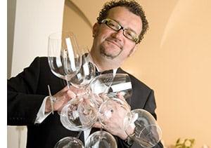 Alexander Adlgasser mit vielen leeren Weingläsern in der Hand