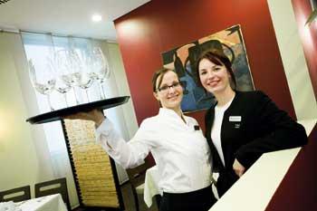 zwei Damen des Hotelpersonals posieren für die Kamera, eine scheint die Kellnerin zu sein mit einem Tablett in der Hand