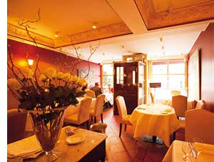 ein Restaurant, vorne links im Bild eine grosse Vase mit gelben Rosen