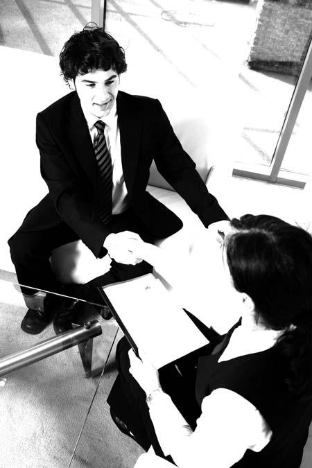 Ein Handschlag zwischen einer Frau und einem Mann, sitzend während eines Bewerbungsgespräches