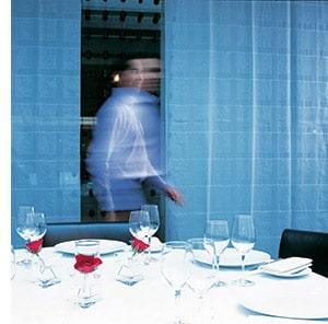 ein gedeckter Tisch, im Hintergrund ein Kellner in Bewegung