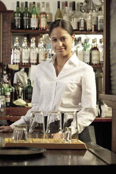 eine Dame steht hinter der Bar