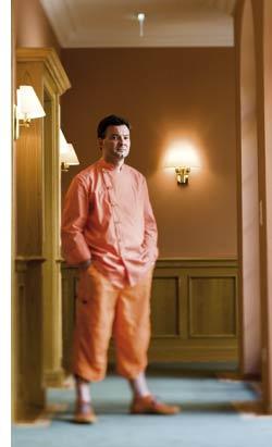 Didi Dorner in orange gekleidet im Hotelflur stehend