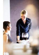Eine Kellnerin bedient eine Dame