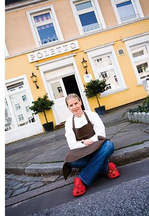 Cornelia Poletto sitzt auf dem Gehsteig vor ihrem Restaurant Poletto