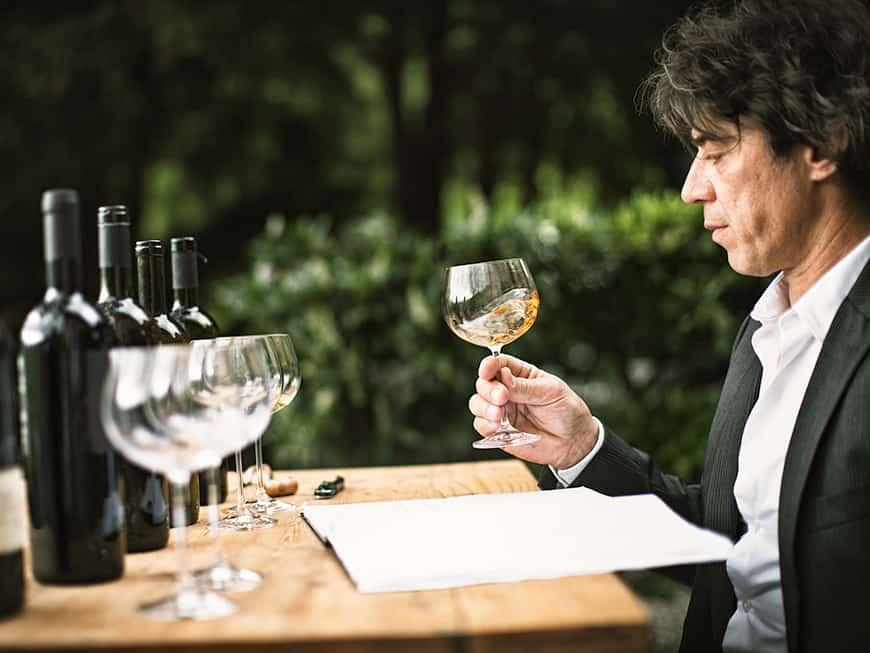 Mann, der ein Weinglas mit darin befindlichen Inhalt ganz genau betrachtet