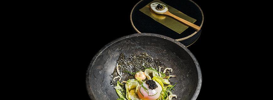 """Joachim Wisslers Gericht """"Landei Miso gebeizt, Lachscreme, Eisbergsalat & d'Aquitaine-Kaviar"""" in einem anthrazitfarbenen tiefen Teller angerichtet. Dazu wird ein Kräcker mit Kaviar gereicht."""